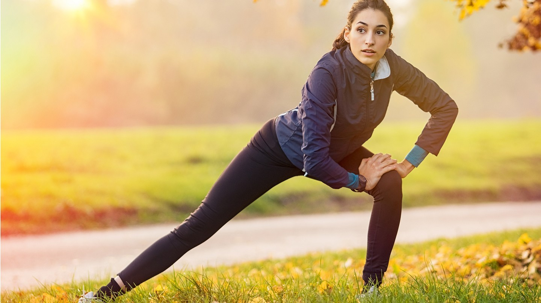 Sport trotz Erkältung: Eine junge Frau macht im Park Dehnübungen.