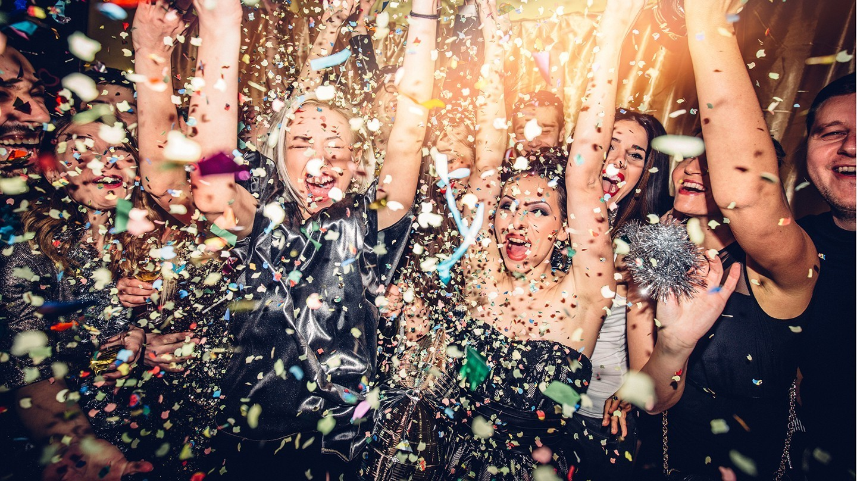 Dem Kater vorbeugen: Junge Frauen von Konfetti umgeben tanzen auf einer Party.