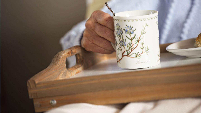 Häusliche Pflege mit Heilpflanzen und Hausmitteln: Fotoausschnitt eines Pflegebedürftigen, der im Bett ein Tablett mit einer großen Tasse Kräutertee hält.