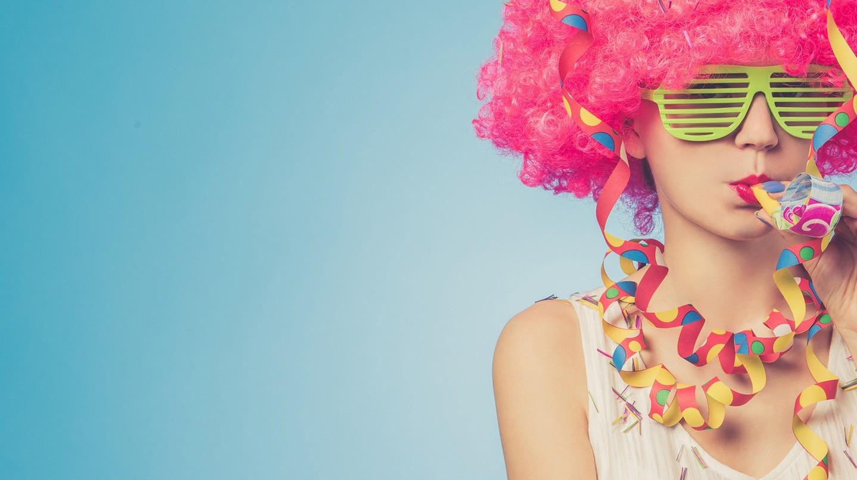 Fasching 2020: Junge Frau mit rosafarbener Perücke, gelber Party-Brille und Luftschlangen um den Hals bläst in Papiertröte.