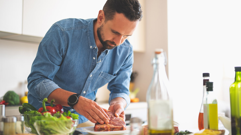 Corona-Infektion durch Fleisch? Mann in Jeanshemd legt in der Küche ein Stück Fleisch auf den Teller.