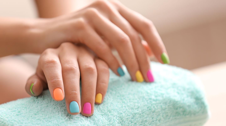 Handekzem: Frauenhände mit bunten Fingernägeln.