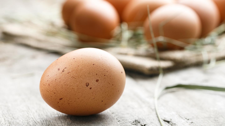 Braune Eier auf Holztisch.