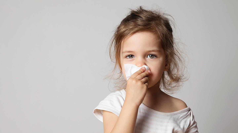 Ein kleines Mädchen hält ein Taschentuch in der Hand und schnäuzt sich die Nase.