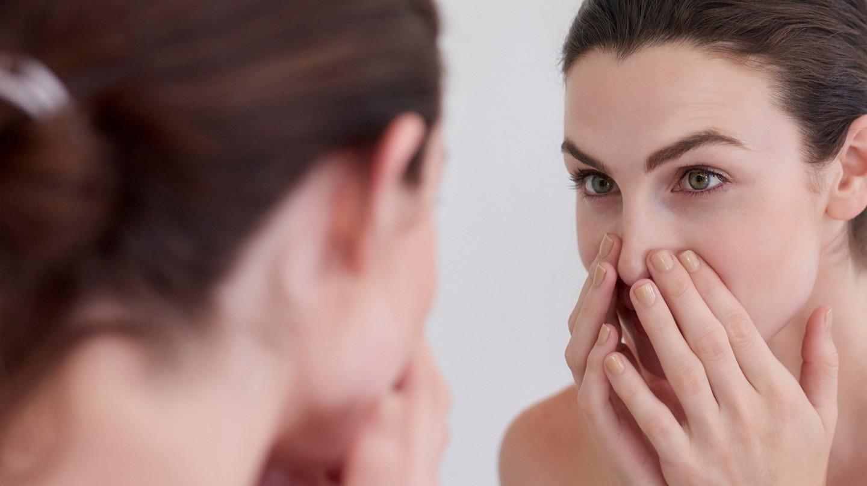 Rosacea: Junge Frau schaut prüfend in den Spiegel und verdeckt mit den Händen den unteren Bereich des Gesichts.